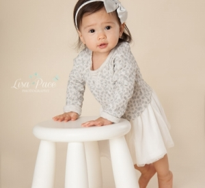 one year old girl standing holding white stool